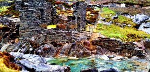 A ruined slate house by a blue pool